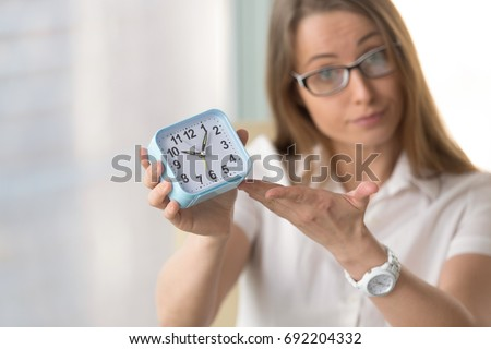 Waiting woman pointing at time, urging to hurry, warning not being late or miss appointment, meeting deadline, finish project due date, focus on clock, time management and punctuality at work concept