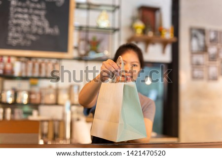 Waitress at counter giving eco friendly paper bag with take away drink in cafe.