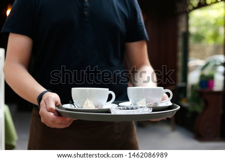 waitress bring the coffee in restaurant closeup. barista at cafeteria with two cups of cappuccino with copy space