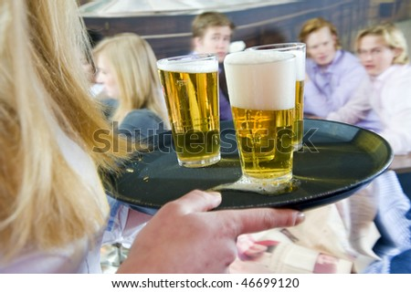 Waitress, bringing a round of beers to a waiting group of customers
