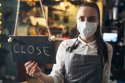 waitress closing cafe or restaurant due coronavirus, holding close sign