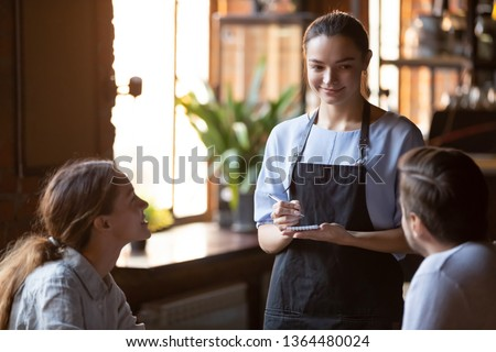Waitress girl wearing apron standing holding notepad and pen ready take order talking with restaurant guests, married couple or heterosexual friends make order communicating with waiting staff concept