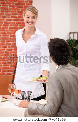 Waitress handing meal to customer
