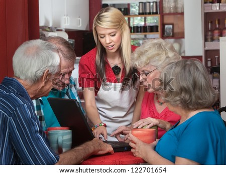 Waitress helping senior citizens with computer in coffeehouse