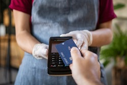 Waitress holding credit card reader machine and wearing protective disposable gloves with client holding credit card. Man hand of customer paying with contactless credit card with NFC technology.