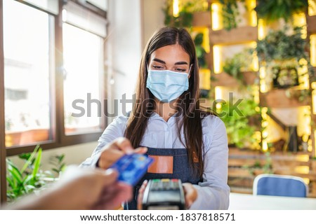 Waitress holding credit card reader machine and wearing protective face mask with client holding credit card. Man hand of customer paying with contactless credit card with NFC technology.