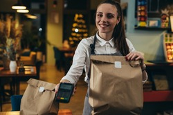 waitress holding prepared takeaway food in eatery. food delivery concept. coronavirus quarantine concept