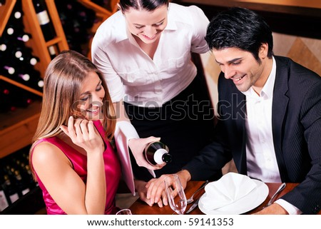 Waitress in a fancy restaurant filling glasses of couple with champagne