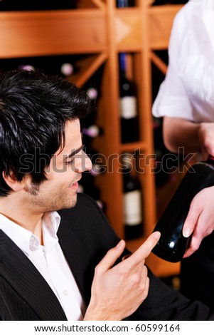 Waitress in a wine bar or restaurant offers a bottle of red wine to a young mediterranean looking man