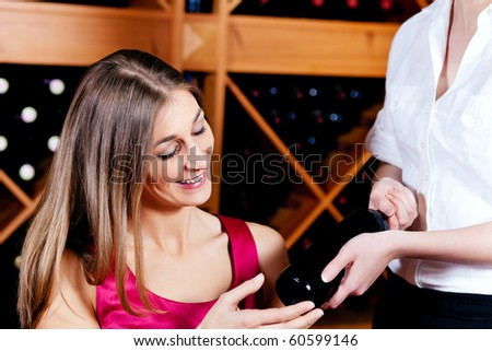 Waitress in a wine bar or restaurant offers a bottle of red wine to a young woman