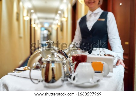 Waitress in uniform delivering tray with food in a room of hotel. Room service. Selective focus on tableware. Horizontal shot