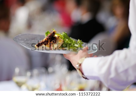Waitress is carrying a plate with meat dish