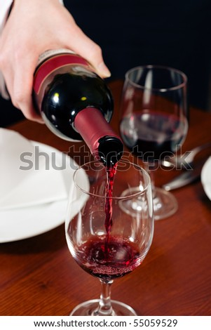 Waitress (just hands to be seen) refills the glass with red wine in a restaurant