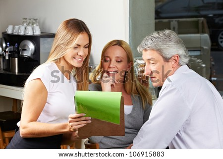 Waitress offering the menu to senior couple and making a recommendation