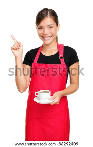 Waitress or barista pointing holding coffee. Woman in apron smiling happy isolated on white background.