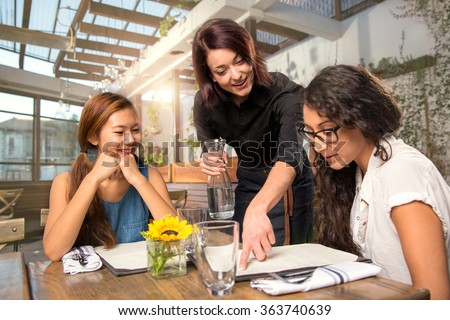 Waitress server helping client patron customer with menu order on sunny patio