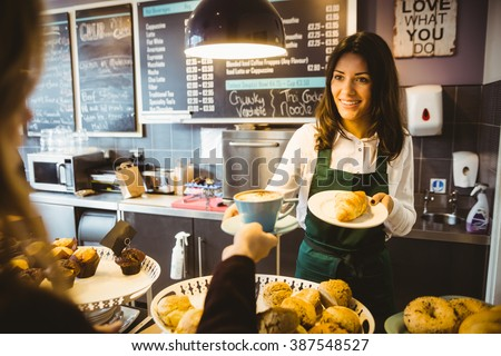 Waitress serving a cup of coffee in cafe #387548527