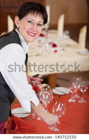 waitress setting the table at restaurant, looking up