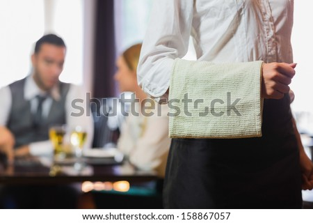 Waitress standing in front of two business people talking in a restaurant