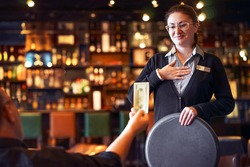 Waitress takes the tip. The waiter female receives a tip from the client at the hotel bar. The concept of service