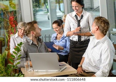 Waitress taking order from businessmen in cafe smiling laptop work