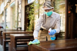Waitress wearing protective face mask and visor while cleaning tables with disinfectant during COVID-19 epidemic.