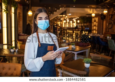 Waitress working on touchpad while wearing protective face mask. Beautiful waitress working at a restaurant wearing a facemask. Waitress wearing a facemask and using a tablet computer Stock fotó ©