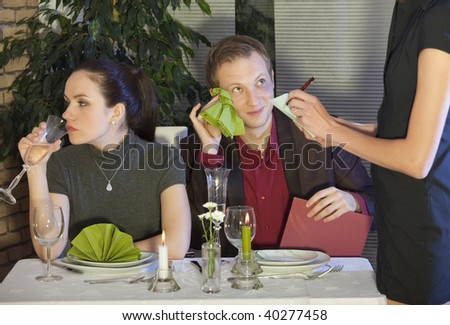 waitress writing a order from couple in restaurant