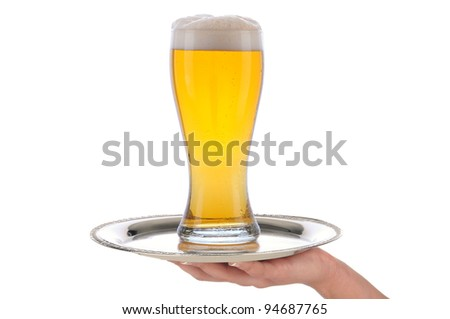 Waitresses hand and arm holding a silver serving tray with a glass of beer. Vertical format over a white background.