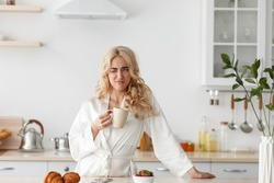 Wake up early, lazy morning, tasty coffee before work for good mood, facial expression. Sleepy disgruntled young pretty blonde female in coat drinks coffee in minimalist kitchen interior, free space