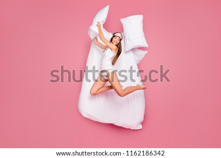 Wake up! Full length size body young gorgeous smiling lady wearing eye mask, fighting with pillow, flying in air. Isolated over pink pastel background