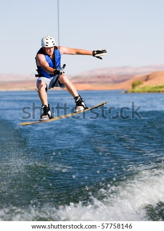 Wakeboarder boarding behind a boat with beautiful Lake Powell in the background at Glen Canyon National Recreation Area, Utah, USA