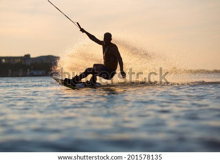 Wakeboarder making tricks on sunset
