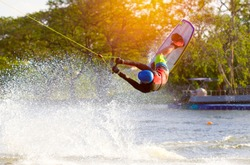 Wakeboarder sportsman jumping with rotation in the cable park, sport and active lifestyle