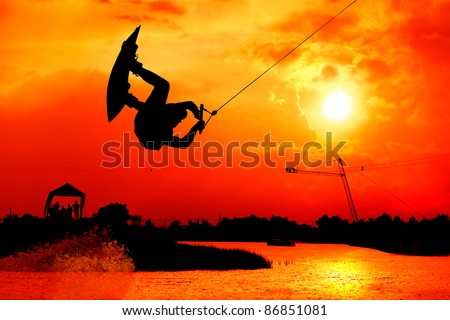 wakeboarding action man surf and jump to  beautiful sky silhouetted , extreme sport