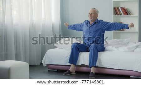 Waking up full of energy cheerful pensioner doing morning gymnastics, new day