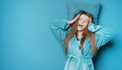 Waking yawning long haired young lady in dressing gown with her head on pillow over isolated background, prevailing blue tone