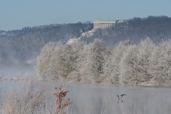 Walhalla memorial in Donaustauf near Regensburg and sea birds on Danube river on clear cold winter day with sun and snow