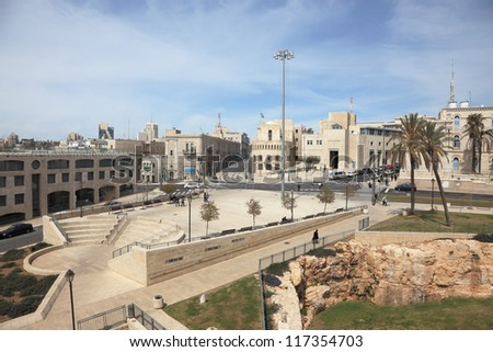 Walk along the walls of ancient Jerusalem. View of the New Jerusalem - modern buildings and people walking