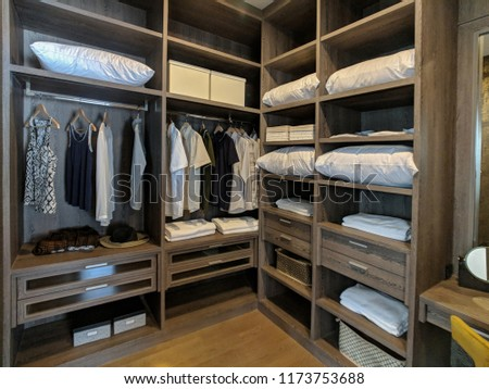 Walk in closet with wooden shelves There are pillows and hanging clothes. #1173753688