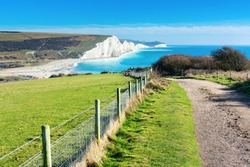 Walk in Cuckmere Haven near Seaford, East Sussex, England. South Downs National park. View of blue sea, cliffs, beach, green fields, selective focus