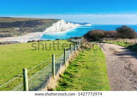 Walk in Cuckmere Haven near Seaford, East Sussex, England. South Downs National park. View of blue sea, cliffs, beach, green fields, selective focus Stockfoto ©