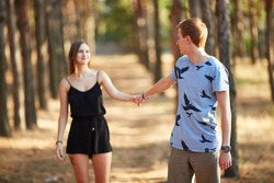 Walk in the beautiful forest. The guy holds his girlfriend's hand.
