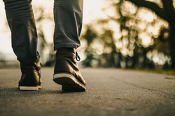 Walk in urban city. Close up view on man's legs in jeans and brown leather boots with sunlight against nature blur background.