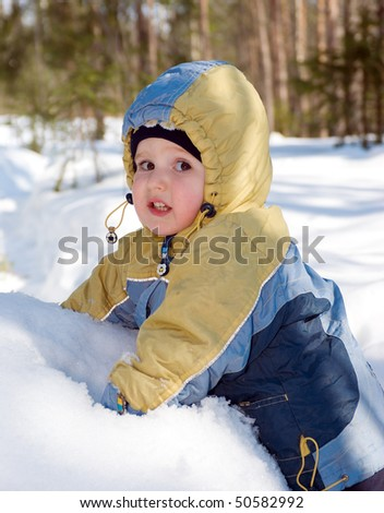 walk in winter wood .small boy plays with snow