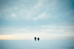 Walk in winter. Young happy people, a guy and a girl are running across the snow-covered field, they are happy. Love story.