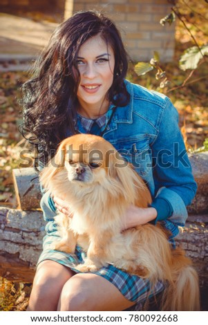 Shutterstock Walk of a young woman with dog at sunset little dog sit with seriously face. Sweet woman with a pet dog walk in the  Park