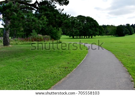 Walk path curved left along the grass background trees and sky - Shutterstock ID 705558103