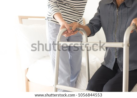 walk training and rehabilitation process, stroke patient use walker with care giver Stockfoto ©