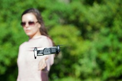 Walk with a drone. A young woman in black glasses launches a low flying drone. Reaches out to a low flying drone, catches. Blurred background. Front view.
